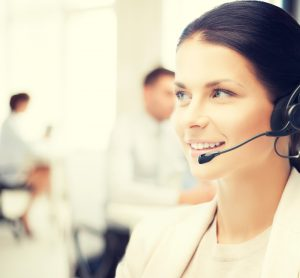 friendly female helpline operator with headphones in call center